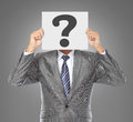 Businessman covering his face with big question mark on gray background Royalty Free Stock Photos