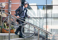 Businessman in crash helmet carrying bicycle down steps Royalty Free Stock Photo