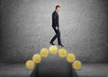 Businessman crossing a bridge made of golden coins Royalty Free Stock Photo
