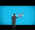 Businessman crossing out the word end on a giant blue wall Stock Photos