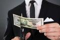 Businessman cutting dollar bill with scissors Royalty Free Stock Photo