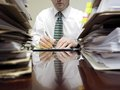 Businessman at desk with piles of files sitting pad paper and Royalty Free Stock Photography