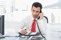Businessman with diary using land line phone at office serious young a bright Stock Image