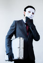 Businessman in disguise mask stealing a confidential suitcase