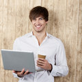 Businessman with disposable cup and laptop portrait of confident young standing against wooden wall Stock Photo