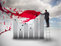 Businessman drawing a chart next to red paint splash and blue sky on the background Royalty Free Stock Photos