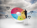 Businessman drawing a colorful pie chart with blue sky on the background Stock Photo