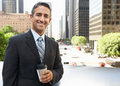 Businessman drinking takeaway coffee outside office smiling Stock Photo
