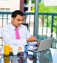 Businessman eating breakfast and working handsome pointin at what he sees on his laptop screen isolated on city background Stock Photo