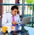 Businessman eating breakfast and working handsome shocked upset at what he see on his laptop screen isolated on city background Stock Image