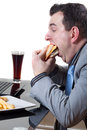 Businessman eating junk food Royalty Free Stock Photos