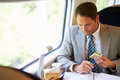 Businessman eating sandwich on train journey and working Royalty Free Stock Photography