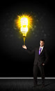 Businessman with an eco friendly bulb hold a shining idea on a black background Royalty Free Stock Photos