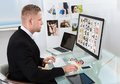 Businessman editing photographs sitting at his desk in front of a large screen monitor Royalty Free Stock Images