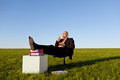 Businessman enjoying coffee on chair in grassy field against sky full length of relaxed clear Royalty Free Stock Images