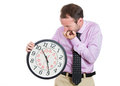 businessman, executive, leader holding and looking anxiously at a clock, biting his nails, pressured by lack of time Royalty Free Stock Photo