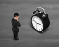 Businessman face alarm clock on concrete ground Stock Photo