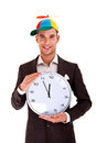 Businessman with fanny hat and wall clock over white background Royalty Free Stock Photo