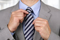 Businessman fixing tie adjusting his necktie concept for anxiety worried meeting or ready for business Stock Photo