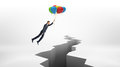 A businessman flies over a huge rift on white surface while holding a bunch of colorful balloons. Royalty Free Stock Photo