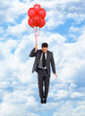 Businessman flying with red balloons in blue cloudy sky Stock Photography