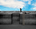 Businessman gazing on top of concrete maze wall with ladder wooden and blue sky Royalty Free Stock Image