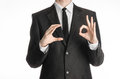 Businessman and gesture topic: a man in a black suit and tie holds his right hand and the left shows a sign of okay isolated on wh Royalty Free Stock Photo