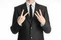 Businessman and gesture topic a man in a black suit with a tie showing a sign with his right hand two or three left hand sign iso Stock Photo