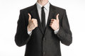 Businessman and gesture topic a man in a black suit with a tie showing two hands thumbs up isolated on white background in studio Royalty Free Stock Image