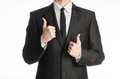 Businessman and gesture topic a man in a black suit with a tie showing two hands thumbs up isolated on white background in studio Stock Image
