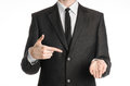 Businessman and gesture topic: a man in a black suit with a tie shows the right hand index finger on his left hand on an isolated Royalty Free Stock Photo