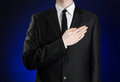 Businessman and gesture topic: a man in a black suit and white shirt, put his hand on his chest on a dark blue background in studi Royalty Free Stock Photo