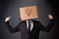 Businessman gesturing with a cardboard box on his head with ligh standing and light bulb Royalty Free Stock Photo