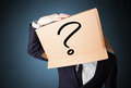 Businessman gesturing with a cardboard box on his head with ques standing and question mark Stock Images