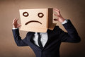 Businessman gesturing with cardboard box on his head with sad fa standing and a face Stock Photo