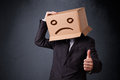 Businessman gesturing with cardboard box on his head with sad fa standing and a face Stock Photos