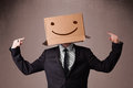 Businessman gesturing with a cardboard box on his head with smil standing and smiley face Royalty Free Stock Photos