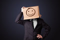 Businessman gesturing with a cardboard box on his head with smil standing and smiley face Stock Photo