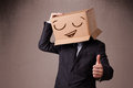 Businessman gesturing with a cardboard box on his head with smil standing and smiley face Royalty Free Stock Image