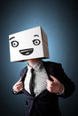 Businessman gesturing with a cardboard box on his head with smil standing and smiley face Stock Image