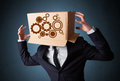 Businessman gesturing with a cardboard box on his head with spur standing and wheels Stock Photo