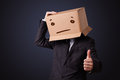 Businessman gesturing with a cardboard box on his head with stra standing and straight face Stock Photo