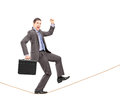 Businessman gesturing happiness on a rope Stock Image