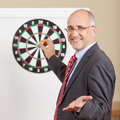 Businessman gesturing while holding dart attached to target on f portrait of happy flipchart in office Royalty Free Stock Photos