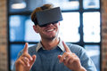 Businessman gesturing while using virtual reality headset Royalty Free Stock Photo