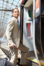 Businessman Getting On Train At Platform Royalty Free Stock Photo
