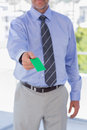 Businessman giving green business card in his office Stock Image