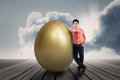 Businessman with golden egg outdoor is standing beside a big Stock Images