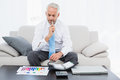 Businessman with graphs and diary sitting in living room concentrated mature the at home Royalty Free Stock Images