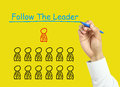 Businessman hand drawing follow the leader concept is with marker on transparent board with yellow background Stock Photo